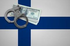 与手铐的芬兰旗子和捆绑美元 打破法律和窃贼罪行的概念 免版税库存照片