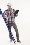 与手钻的建设者在梯子 免版税库存照片