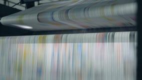 与打印的报纸的滚动的传动机工作在印刷品办公室 影视素材
