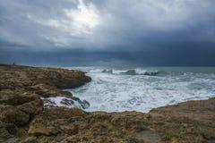 与打反对岩石和峭壁的风雨如磐的波浪的重的云彩 库存照片