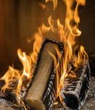 与打在bushwood日志外面的高黄色火焰的开阔的壁炉 库存图片