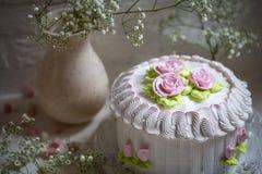 与打好的奶油和玫瑰色奶油的蛋糕 库存图片