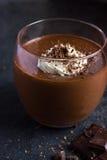 与打好的奶油的可口巧克力布丁在玻璃 图库摄影