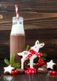 与打好的奶油的热巧克力在有红色镶边秸杆的古板的减速火箭的瓶 圣诞节假日饮料和姜饼b 库存图片