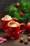 与打好的奶油的热巧克力在红色杯子 中看不中用的物品蓝色圣诞节构成玻璃 免版税图库摄影