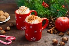 与打好的奶油的热巧克力在红色杯子 中看不中用的物品蓝色圣诞节构成玻璃 库存图片
