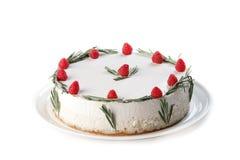 与打好的奶油的白蛋糕装饰用迷迭香莓和小树枝在被隔绝的白色背景的 免版税库存照片