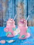 与打好的奶油,糖的桃红色独角兽奶昔和洒 图库摄影