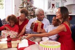 与打开圣诞节礼物的祖父母的家庭 免版税库存图片