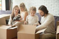 与打开箱子的孩子的愉快的家庭移动新的家 免版税库存照片
