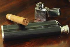 与打火机和臀部烧瓶的古巴雪茄。 免版税库存照片