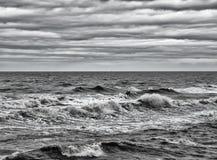 与打破风雨如磐的波浪的海景与苍白冬天天空 库存图片