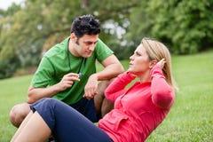 与执行仰卧起坐的妇女的健身教练 库存图片