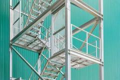与扶手栏杆的外部金属楼梯在一排工厂厂房 免版税库存照片
