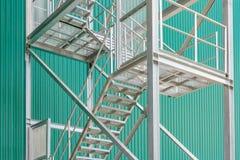 与扶手栏杆的外部金属楼梯在一排工厂厂房 库存照片