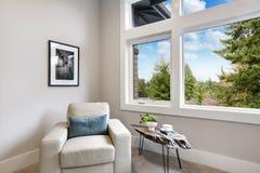 与扶手椅子和大窗口的轻的现代主卧室内部 库存照片