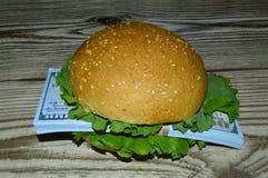 与批的一个汉堡美元咬住一个人 免版税库存图片