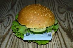 与批的一个汉堡美元咬住一个人 库存图片