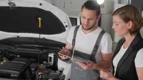 与技工的顾客通信,汽车修理,谈论工作 影视素材