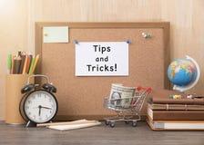 与技巧的纸笔记和在黄柏的把戏词上与警报 免版税库存照片