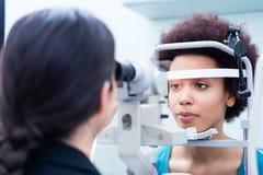 与折射计的眼镜师测量的妇女眼睛 免版税库存图片