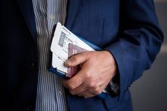 与护照的商人和登舱牌在机场 免版税库存照片