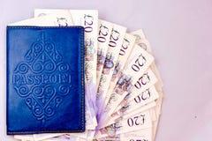 与护照的英国磅在蓝色盖子 库存照片