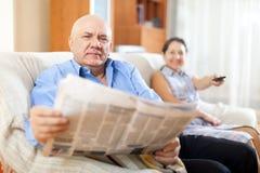与报纸一起的成熟夫妇 免版税库存图片