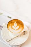 与报纸的热的拿铁艺术咖啡在木桌,葡萄酒上和 免版税库存照片