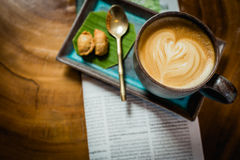 与报纸的热的拿铁艺术咖啡在木桌,葡萄酒上和 库存照片
