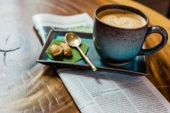 与报纸的热的拿铁艺术咖啡在木桌,葡萄酒上和 库存图片