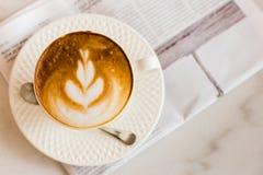 与报纸的热的拿铁艺术咖啡在木桌,葡萄酒上和 图库摄影