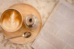 与报纸的热的拿铁艺术咖啡在木桌,葡萄酒上和 免版税库存图片