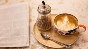 与报纸的热的拿铁艺术咖啡在木桌,葡萄酒上和 免版税图库摄影