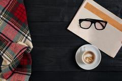 与报纸,咖啡杯,围巾,玻璃的工作区 时髦的办公桌 秋天或冬天概念 平的位置,顶视图 库存图片