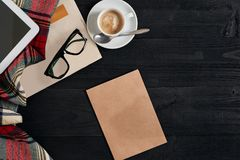 与报纸,咖啡杯,围巾,玻璃的工作区 时髦的办公桌 秋天或冬天概念 平的位置,顶视图 库存照片