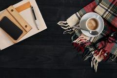 与报纸,咖啡杯,围巾,玻璃的工作区 时髦的办公桌 秋天或冬天概念 平的位置,顶视图 免版税库存照片