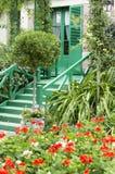 与报道前方的花的五颜六色的房子入口 库存图片