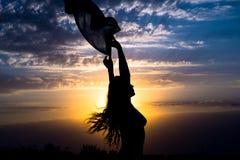 与披肩的女孩剪影在美丽的多云蓝天背景与黄色金黄日落的 库存图片