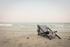 与披肩的海滩睡椅坐海海滩视图 口气和vignet 免版税库存图片