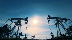 与抽汽油的两个井架的被日光照射了风景 能量,石油,气体,燃料抽的船具 股票录像