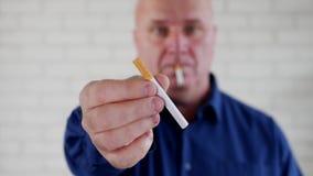 与抽烟一个的人的模糊的照片提供一根新的香烟为一个吸烟者人 影视素材
