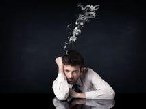 与抽烟的头的沮丧的商人 免版税库存照片