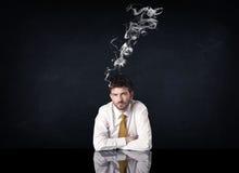与抽烟的头的沮丧的商人 图库摄影