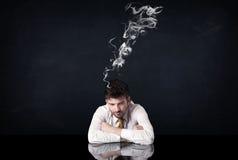与抽烟的头的沮丧的商人 库存照片
