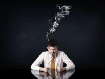 与抽烟的头的沮丧的商人 免版税库存图片