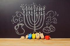 与抽陀螺dreidel的创造性的犹太假日光明节背景在有手图画的黑板 免版税图库摄影