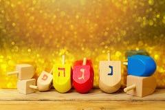 与抽陀螺dreidel的犹太假日光明节背景在金黄bokeh的木桌上 库存图片
