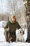 与拉布拉多猎犬和猎枪的猎人在冬天森林里 库存照片