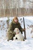与拉布拉多猎犬和猎枪的猎人在冬天森林里 库存图片